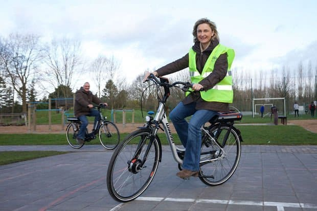 Easy E-Biking - woman riding e-bike yellow vest, helping to make electric biking practical and fun