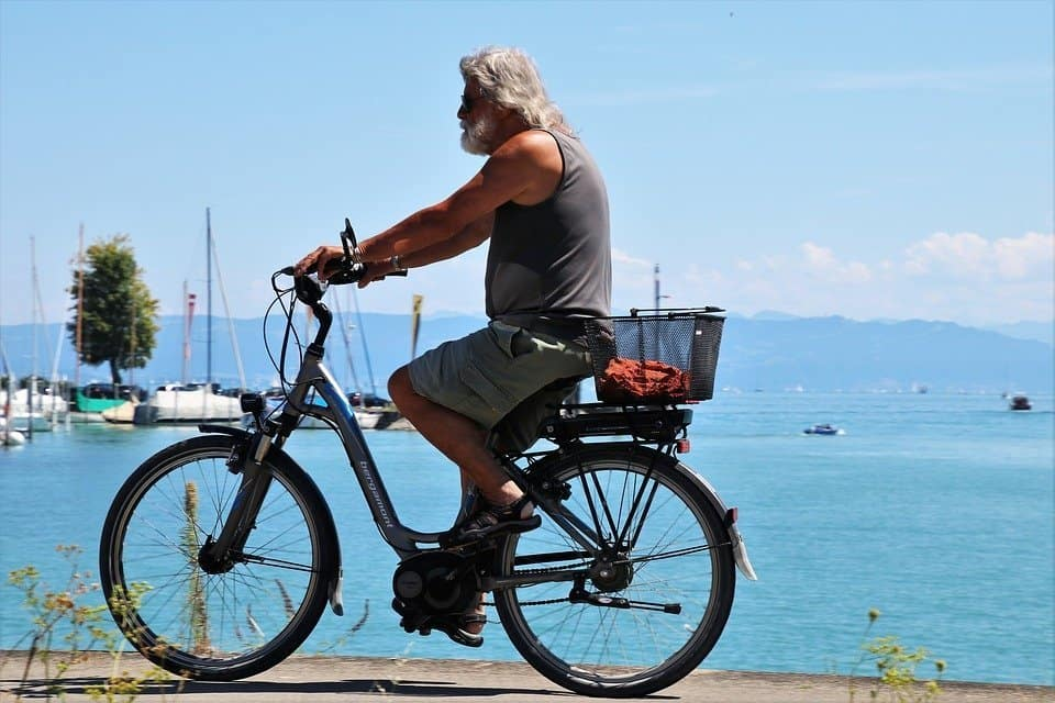 Easy E-Biking - man e-cycling along sea, helping to make electric biking practical and fun