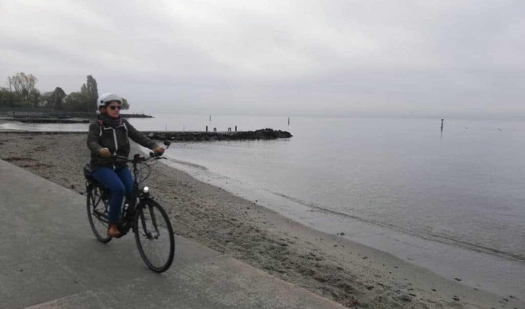 Easy E-Biking - woman e-biking lake coast, helping to make electric biking practical and fun